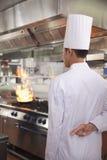 Hintere Ansicht des Chefs mit den Fingern gekreuzt als Pan Catches Fire in der Küche Lizenzfreie Stockfotografie