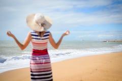 Hintere Ansicht des defocused meditierenden weiblichen genießenden Sommerstrandes und -sonne Lizenzfreie Stockfotos