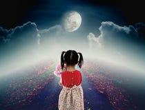 Hintere Ansicht des einsamen Kindes mit trauriger Geste der Puppe auf Bahn mit Stockbild