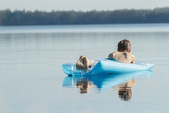 Hintere Ansicht des entspannten Teenagers draußen schwimmend auf azurblauen aufblasbaren Poolaufenthaltsraum Stockfotografie