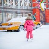 Hintere Ansicht des entzückenden kleinen Mädchens, das den Eislauf genießt Lizenzfreie Stockfotografie