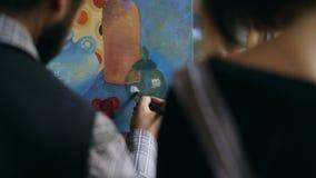 Hintere Ansicht des erfahrenen Künstlermannes, der jungem Mädchen die Grundlagen der Malerei im Kunststudio unterrichtet und zeig Stockfoto