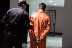 hintere Ansicht des führenden Gefangenen des Gefängnisaufsehers in den Handschellen lizenzfreie stockbilder