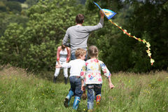 Hintere Ansicht des Familien-Fliegen-Drachens in der Landschaft Stockfotos