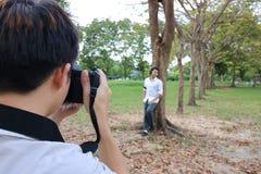 Hintere Ansicht des Fotografen ein Foto des jungen Mannes im Sommerpark machend Stockfotografie