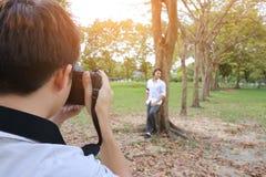 Hintere Ansicht des Fotografen ein Foto des jungen Mannes im Sommerpark machend Sonnenscheineffekt Weinleseton Lizenzfreie Stockbilder