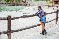 Hintere Ansicht des Frauencowgirls nahen Zaun auf Ranch stehend stockfotos