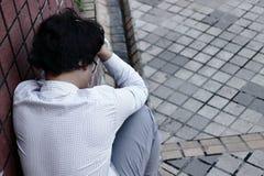 Hintere Ansicht des frustrierten erschöpften asiatischen Geschäftsmannes in der Krise mit den Händen auf Stirn lizenzfreies stockfoto