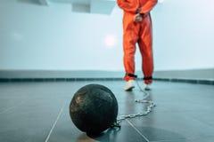 hintere Ansicht des Gefangenen in der orange Uniform mit Gewicht begrenzt lizenzfreie stockbilder