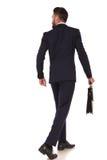 Hintere Ansicht des gehenden Geschäftsmannes, der einen Aktenkoffer hält Stockfotos