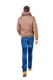 Hintere Ansicht des gehenden gutaussehenden Mannes in den Jeans und in der Jacke Stockbild