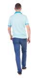 Hintere Ansicht des gehenden gutaussehenden Mannes in den Jeans und in einem Hemd Stockfoto