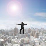 Hintere Ansicht des Geschäftsmannes balancierend auf Drahtseil Stockfoto