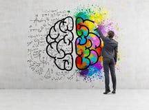 Hintere Ansicht des Geschäftsmannes bunte Gehirnikone auf Beton zeichnend Stockfoto
