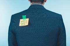 hintere Ansicht des Geschäftsmannes in der Klage mit Anmerkung mit Rückseite der Aprilscherztagesbeschriftung an, Aprilscherze lizenzfreie stockfotografie