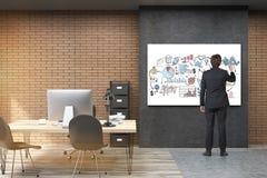 Hintere Ansicht des Geschäftsmannes im schwarzen Anzug, der ein Motivpo zeichnet Lizenzfreie Stockbilder