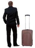 Hintere Ansicht des Geschäftsmannes im schwarzen Anzug, der mit suitcas reist Lizenzfreie Stockbilder
