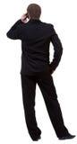 Hintere Ansicht des Geschäftsmannes im schwarzen Anzug sprechend am Handy Lizenzfreies Stockbild