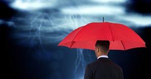 Hintere Ansicht des Geschäftsmannes roten Regenschirm gegen digitales zusammengesetztes Bild von Wolken halten Stockfotografie