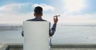 Hintere Ansicht des Geschäftsmannes sitzend auf Stuhl und rauchender Zigarre beim Betrachten von Meer gegen Himmel Stockfotografie