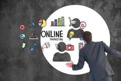 Hintere Ansicht des Geschäftsmannes verschiedene Online-Marketings-Ikonen auf Tafel betrachtend Stockfoto
