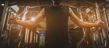 Hintere Ansicht des gesunden muskulösen jungen Mannes mit seinen Armen heraus ausgedehnt, starker athletischer Manneignungs-Model stockbild