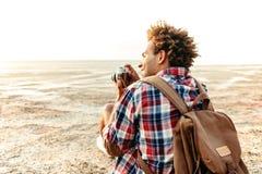 Hintere Ansicht des glücklichen Mannes Fotos auf dem Strand machend Stockbild