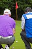 Hintere Ansicht des Golfspielers und des Transportgestells. Stockfotos