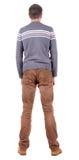 Hintere Ansicht des gutaussehenden Mannes in der Strickjacke und in Jeans, die oben schauen. Lizenzfreie Stockbilder
