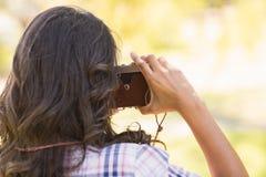Hintere Ansicht des hübschen Brunette im Park unter Verwendung der Retro- Kamera Lizenzfreie Stockfotos