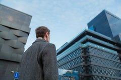 Hintere Ansicht des jungen überzeugten Mannführers, der nahe dem Bürogebäude steht Ansicht von unten lizenzfreie stockbilder