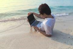 Hintere Ansicht des jungen asiatischen Mannes mit dem Laptop, der sich auf dem sandigen des Strandes hinlegt stockfoto