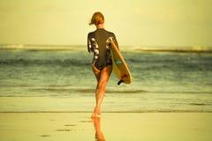 Hintere Ansicht des jungen attraktiven und sportlichen Surfermädchens im kühlen Badeanzug am tragenden Brandungsbrett des Strande stockfoto