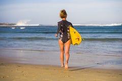 Hintere Ansicht des jungen attraktiven und sportlichen Surfermädchens im kühlen Badeanzug am tragenden Brandungsbrett des Strande stockbilder