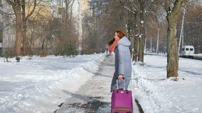 Hintere Ansicht des jungen erwachsenen Mädchens im warmen Mantel und im bunten gestrickten scaft gehend, ihren großen violetten K stock footage