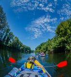 Hintere Ansicht des Jungen Kayak fahrend auf dem Fluss an einem sonnigen Tag während der Sommerferien Lizenzfreie Stockbilder