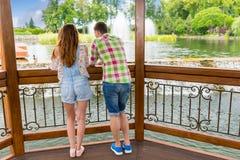 Hintere Ansicht des jungen männlichen und weiblichen Lehnens auf Geländer des wo Stockfotos