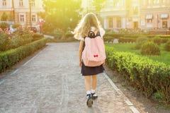 Hintere Ansicht des jungen Schulmädchens in der Uniform mit dem Rucksack, der zu geht Lizenzfreie Stockbilder