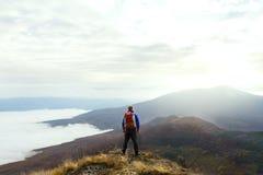 Hintere Ansicht des jungen touristischen Wanderers mit dem Rucksack, der auf die Oberseite des Berges steht und schönes Gelb betr stockbild