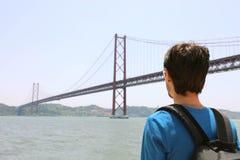 Hintere Ansicht des jungen Wanderermannes, der Brücke betrachtet Reisender oder Tourist mit Rucksack auf der Ufergegend in Lissab stockfoto