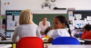 Hintere Ansicht des kaukasischen Schulmädchens lächelnd im Klassenzimmer 4k stock video footage