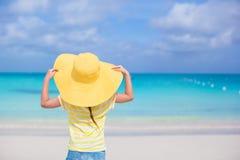 Hintere Ansicht des kleinen Mädchens in einem großen gelben Strohhut Stockfoto
