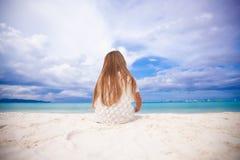 Hintere Ansicht des kleinen netten Mädchens, das auf dem Strand siiting ist stockfotografie