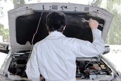 Hintere Ansicht des Kraftfahrzeug-Mechanikermannes, der Schlüssel gegen Auto in der offenen Haube hält Stockbild