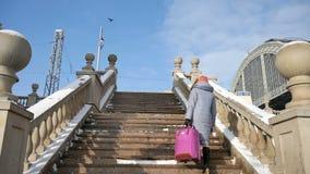 Hintere Ansicht des lächelnden weiblichen Reisenden im warmen Mantel und in der bunten Strickmütze und des scaft, das oben durch  stock video