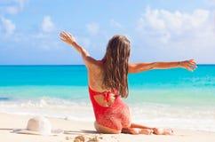 Hintere Ansicht des langhaarigen Mädchens im roten Badeanzug auf tropischem karibischem Strand Stockbild