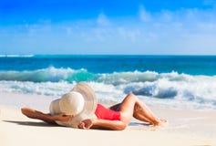 Hintere Ansicht des langhaarigen Mädchens im roten Badeanzug und im Strohhut auf tropischem karibischem Strand Lizenzfreie Stockfotografie
