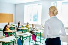 hintere Ansicht des Lehrers Kinder betrachtend lizenzfreies stockbild