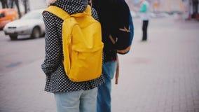 Hintere Ansicht des lokalen Mannes und der Frau mit dem hellen gelben Rucksackstandabschluß, der zusammen an einem kalten Tag des stock footage