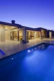 Hintere Ansicht des Luxuslandhauses in der Nacht mit Swimmingpool Lizenzfreie Stockfotos